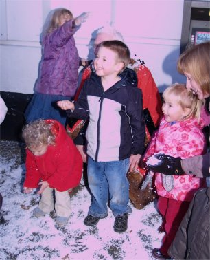 Children enjoy the snow with the Mayor